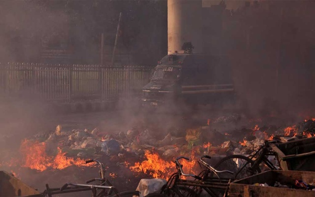A police vehicle moves past burning debris that was set on fire by demonstrators in a riot affected area after fresh clashes erupted between people demonstrating for and against a new citizenship law in New Delhi, India, Feb 25, 2020. REUTERS/Danish Siddiqui