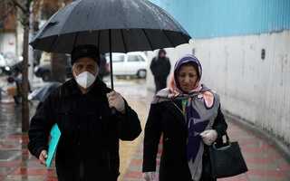 An Iranian man wears protective mask to prevent contracting coronavirus, as he walks in the street in Tehran, Iran Feb 25, 2020. REUTERS