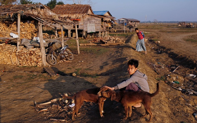 A boy from Ta Dar U village pets a dog after villagers relocated their houses inland in Bago, Myanmar, Feb 6, 2020. REUTERS