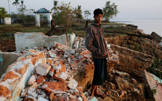 Myo Zaw, 15, stands amid the ruins of a monastery after the riverbank is was located on collapsed into the water in Ta Dar U village,Bago, Myanmar, Feb 6, 2020. REUTERS