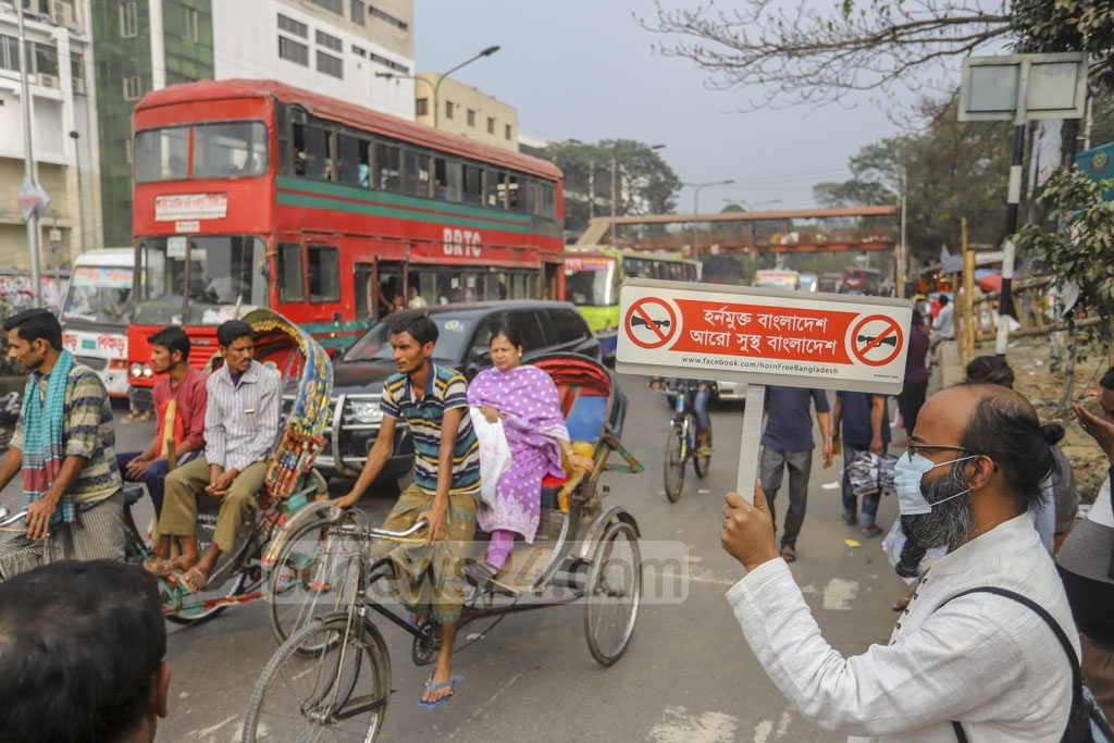 A man holding a placard in Dhaka's Shahbagh urging drivers to cut down on honking car horns as part of a self-initiative to curb noise pollution in the capital. Photo: Asif Mahmud Ove