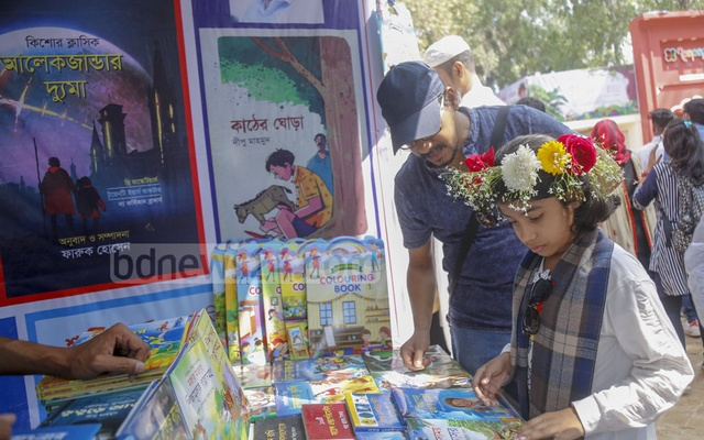 A child browsing a book at a stall at the Ekushey Book Fair during children's hour on Friday. Photo: Mahmud Zaman Ovi