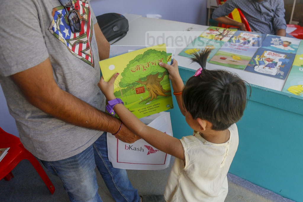 A child packing a book in a bag during children's hour at the Ekushey Book Fair on Friday. Photo: Mahmud Zaman Ovi