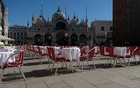 Waiters stand by an empty restaurant in St Mark's Square, which would usually be full of tourists, as a coronavirus outbreak continues to grow in the country, in Venice, Italy, Feb 27, 2020. REUTERS