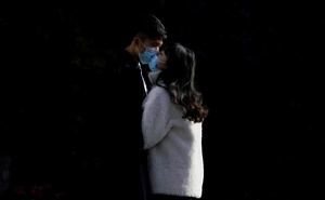 File Photo: A couple wearing masks kiss at a main shopping area, in downtown Shanghai, China, as the country is hit by an outbreak of a new coronavirus, February 16, 2020. Reuters