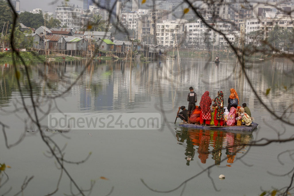 Residents of the Korail slum in Dhaka's Mohakhali crossing Gulshan Lake by a flimsy raft made of thermocol sheets and driven by teenaged boys who charge Tk 10 per passenger. Photo: Mahmud Zaman Ovi