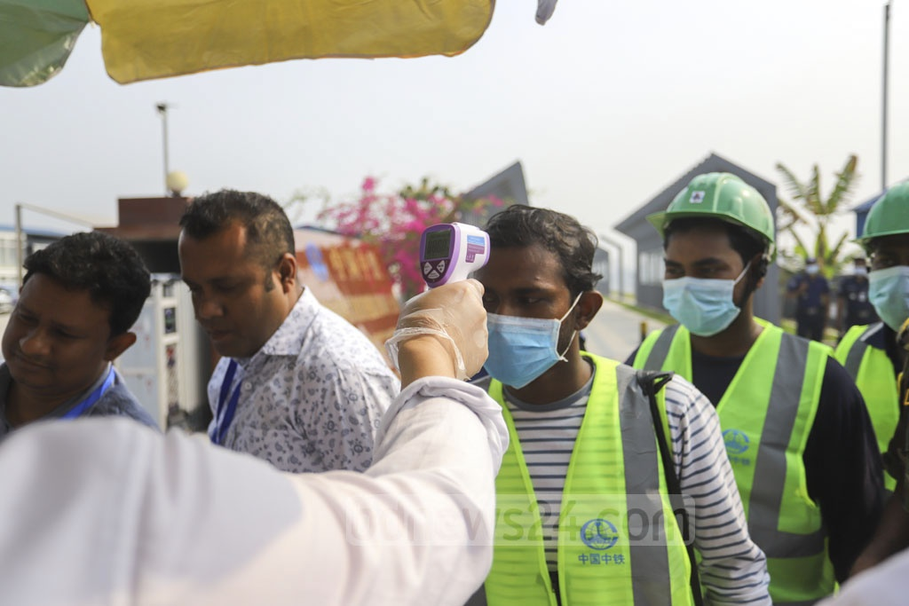 Health workers check temperature of all at the entrance to the Padma Bridge Rail Link Project site in Dhaka's Keraniganj as part of precautionary measures to prevent a possible outbreak of COVID-19. Photo: Asif Mahmud Ove