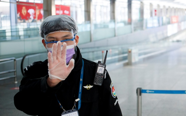 A security officer wearing protective gear gestures at the photographer at the arrival hall of Beijing Capital Airport, as the country is hit by an outbreak of the novel coronavirus, in Beijing, China, March 4, 2020. Reuters