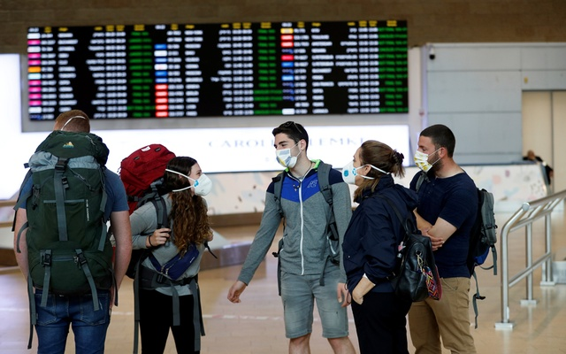Travellers wearing masks chat in the arrivals terminal after Israel said it will require anyone arriving from overseas to self-quarantine for 14 days as a precaution against the spread of coronavirus, at Ben Gurion International airport in Lod, near Tel Aviv, Israel Mar 10, 2020. REUTERS