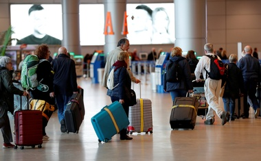 Travelers walk with their suitcases in the departures terminal after Israel said it will require anyone arriving from overseas to self-quarantine for 14 days as a precaution against the spread of coronavirus, at Ben Gurion International airport in Lod, near Tel Aviv, Israel Mar 10, 2020. REUTERS