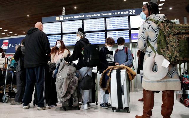 Travellers wearing protective face masks line up at the Delta Air Lines ticketing desk inside Terminal 2E at Paris Charles de Gaulle airport in Roissy, after the US banned travel from Europe, as France grapples with an outbreak of coronavirus disease (COVID-19), March 12, 2020. Reuters