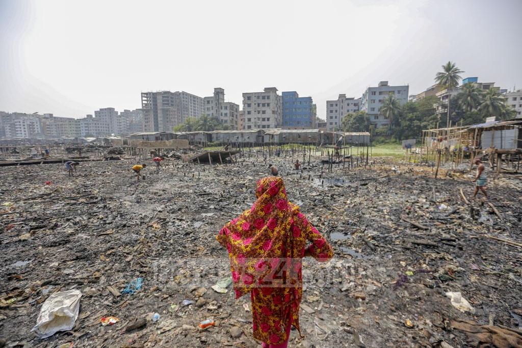A woman stands on the place where her shanty had been before it was burnt down. Photo: Mahmud Zaman Ovi