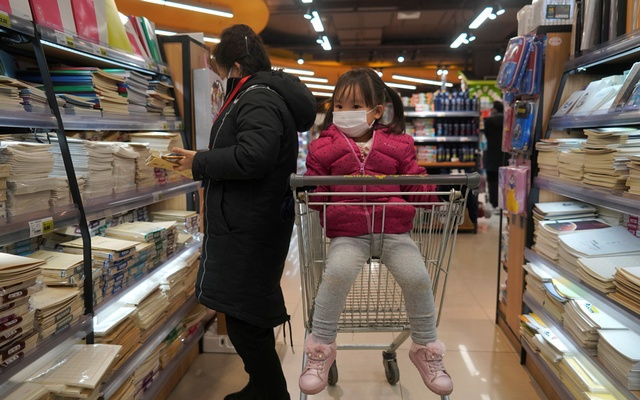 A child wearing a face mask sits in a shopping trolley inside a shop, as the country is hit by a novel coronavirus outbreak in Beijing, China March 1, 2020. Reuters