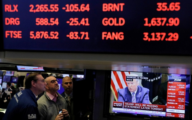 FILE PHOTO: US President Donald Trump is seen on a screen under trading figures during his meeting with bank executives as traders work on the floor of the New York Stock Exchange (NYSE) in New York City, New York, US, March 11, 2020. REUTERS