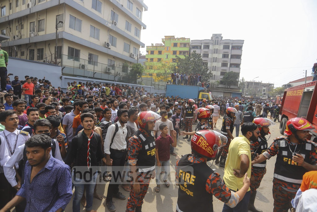 Onlookers gathered when a fire engulfed a warehouse used for storing 'Jhut', a local term for scraps produced in apparel factories, in Dhaka's Mirpur-10 on Saturday. Photo: Asif Mahmud Ove