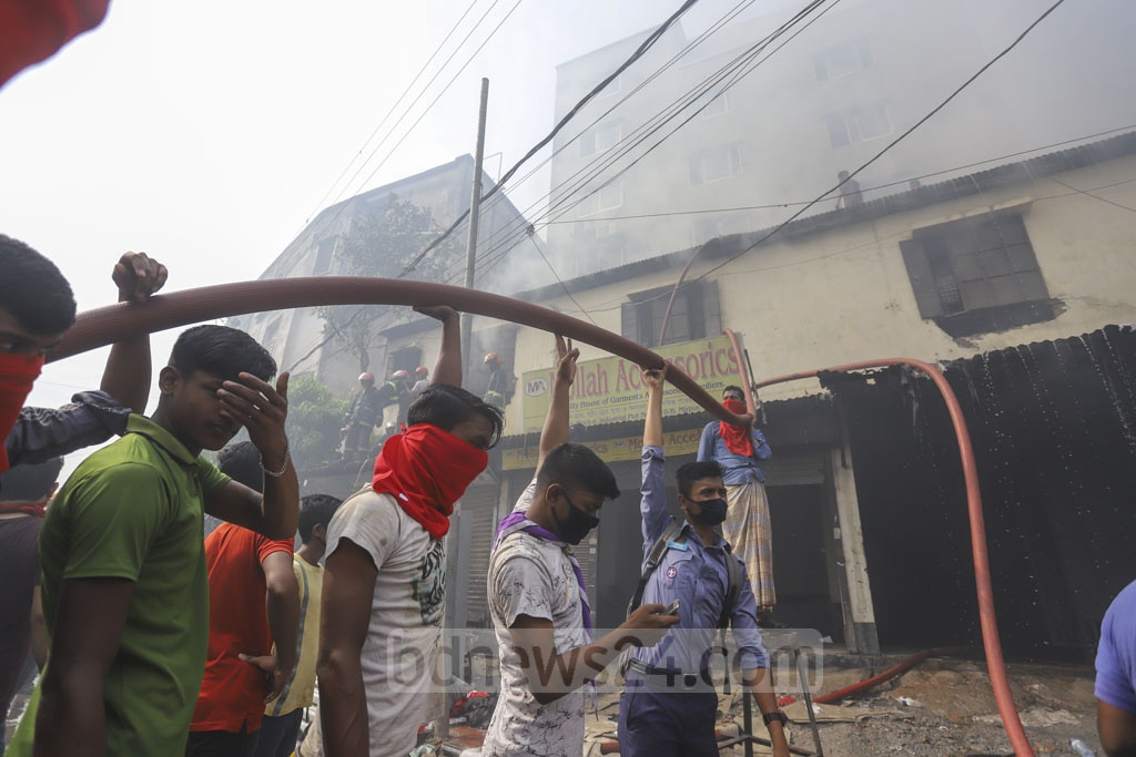 Locals help firefighters in their efforts to douse flames that engulfed a warehouse used for storing 'Jhut', a local term for scraps produced in apparel factories, in Dhaka's Mirpur-10 on Saturday. Photo: Asif Mahmud Ove