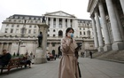 A woman, wearing a protective face mask, walks in front of the Bank of England, following an outbreak of the coronavirus, in London, Britain March 11, 2020. Reuters