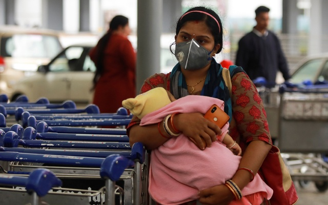 A passenger wearing a protective mask holds a baby as she waits outside an airport following an outbreak of the coronavirus disease (COVID-19), in New Delhi, India, Mar 14, 2020. REUTERS