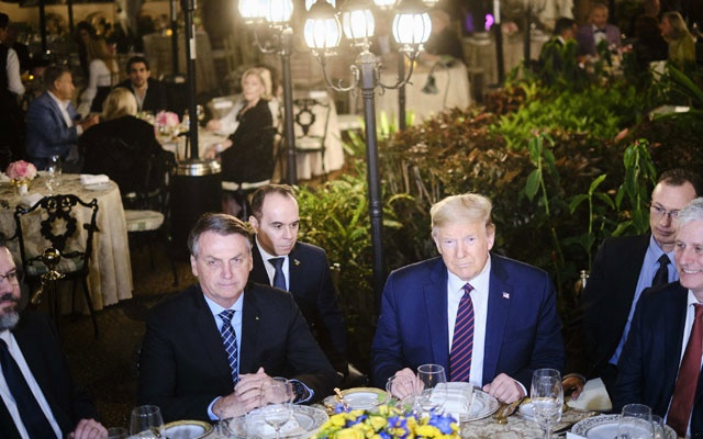 President Donald Trump and Brazilian President Jair Bolsonaro, left, during a dinner at Trump's Mar-a-Lago resort in Palm Beach, Fla., March 7, 2020. Trump's weekend getaway at the resort put him in contact with several people who later tested positive for the virus. (T.J. Kirkpatrick/The New York Times)
