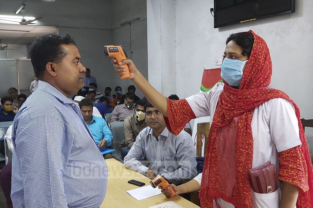 Medical workers use handheld thermometers to check temperature of visitors at the Secretariat in Dhaka on Wednesday as part of coronavirus precaution.