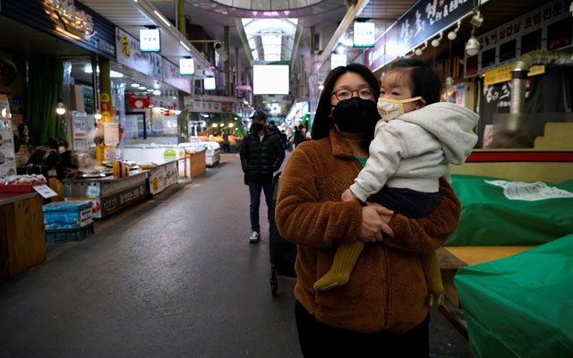 A mother and her child wearing masks to prevent contacting the coronavirus, shop at a traditional market in Seoul, South Korea, February 24, 2020. Reuters