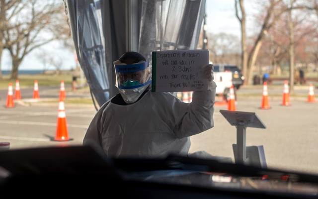 A health care worker holds up a message at a drive-through testing centre for the coronavirus in New Rochelle, NY, on Monday, Mar 16, 2020. The New York Times