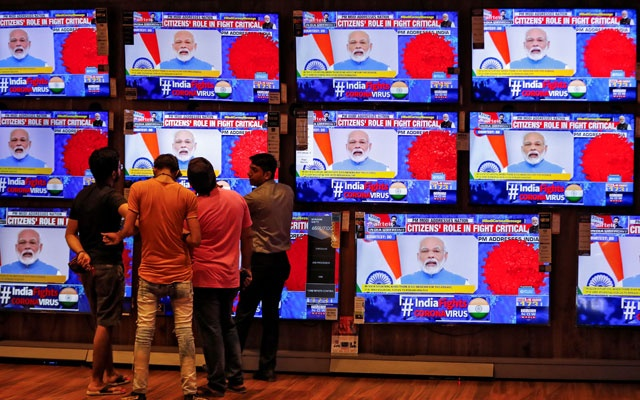 People watch Indian Prime Minister Narendra Modi addressing the nation amid concerns about the spread of coronavirus disease (COVID-19), on TV screens inside a showroom in Ahmedabad, India, March 19, 2020. Reuters