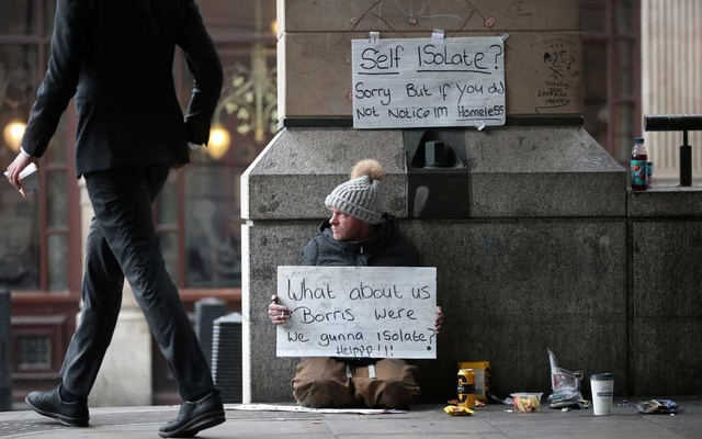 A homeless man holds up a sign outside Westminster underground station as the spread of the coronavirus disease (COVID-19) continues, in London, Britain, Mar 19, 2020. REUTERS