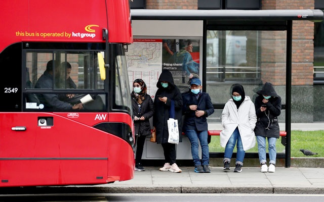 People wearing protective face mask wait for a bus in front of the St. Paul's Cathedral, as the number of coronavirus disease (COVID-19) cases grow around the world, in London, Britain, March 19, 2020. Reuters