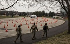 Members of the National Guard walk by a drive-through coronavirus testing site at Bergen Community College, in Paramus, NJ, on Friday, Mar 20, 2020. The New York Times