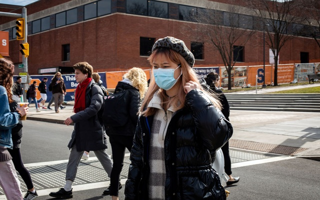A woman wears a protective face mask as students prepare for Spring Break and an extended period of online classes due to coronavirus at Syracuse University, New York, US, Mar 12, 2020. REUTERS