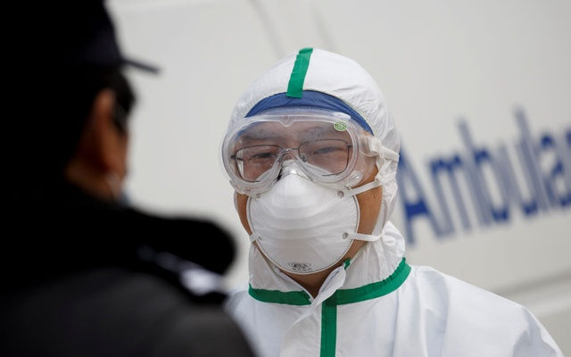 A hospital staff member in protective garments talks to a police officer at a checkpoint to the Hubei province exclusion zone at the Jiujiang Yangtze River Bridge in Jiujiang, Jiangxi province, China, as the country is hit by an outbreak of a new coronavirus, February 1, 2020. REUTERS