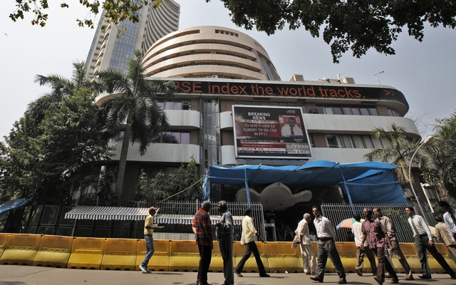 Commuters walk past the BSE building in Mumbai. REUTERS