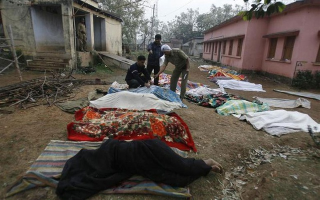 Policemen look at bodies in the grounds of a police camp that was attacked by Maoist rebels in Silda village, about 200 km west of Kolkata, February 16, 2010. About 100 Maoist rebels, many riding motorcycles, stormed the police camp in West Bengal on Monday and killed at least 15 policemen as they fired indiscriminately and set fire to the site. REUTERS