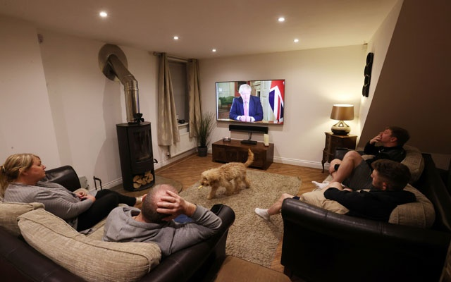 A family watches British Prime Minister Boris Johnson's press conference as the spread of coronavirus disease (COVID-19) continues in Newcastle-under-Lyme, Britain March 23, 2020. Reuters