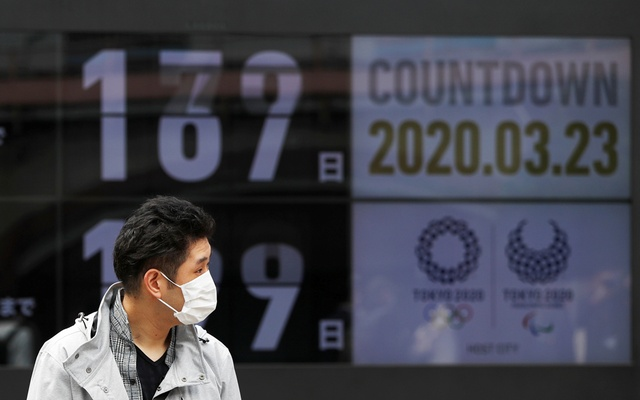 A passersby, wearing a face mask due to the outbreak of the coronavirus disease (COVID-19), walks past a screen counting down the days to the Tokyo 2020 Olympic Games in Tokyo, Japan Mar 23, 2020. REUTERS