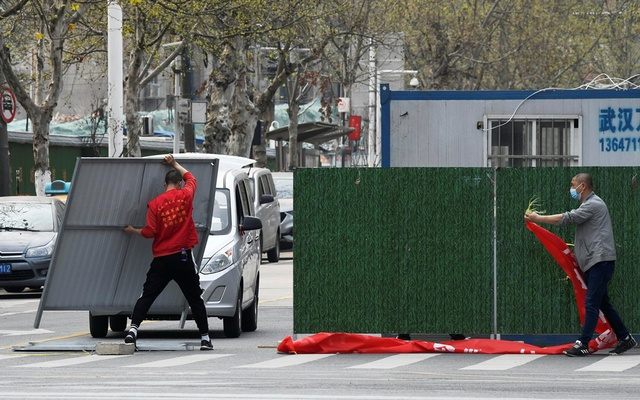 Workers wearing face masks remove barriers on a street in Wuhan, the epicentre of the novel coronavirus disease (COVID-19) outbreak, as the city has started to loosen its lockdown, in Hubei province, China Mar 21, 2020. REUTERS