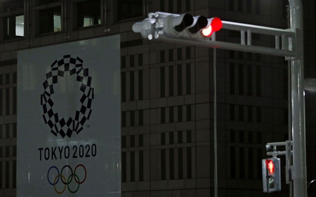 A banner for the upcoming Tokyo 2020 Olympics is seen behind traffic lights, following an outbreak of the coronavirus disease (COVID-19), in Tokyo, Japan, March 23, 2020. Reuters