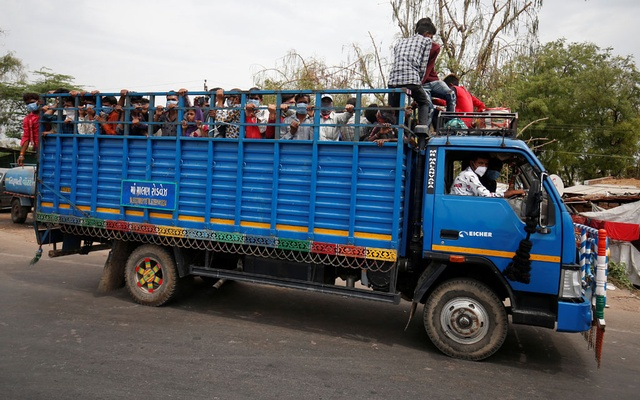 Migrant workers and their families board a truck to return to their villages after India ordered a 21-day nationwide lockdown to limit the spreading of coronavirus disease (COVID-19), in Ahmedabad, India, Mar 25, 2020. REUTERS