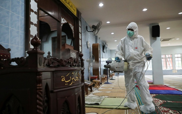 A worker sprays disinfectant at a mosque, which is closed during the movement control order due to the outbreak of the coronavirus disease (COVID-19), in Kuala Lumpur, Malaysia Mar 24, 2020. REUTERS