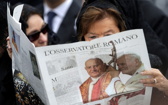 A woman reads a copy of the Vatican newspaper L'Osservatore Romano as she waits for the canonisation ceremony in St Peter's Square at the Vatican, Apr 27, 2014. REUTERS/FILE