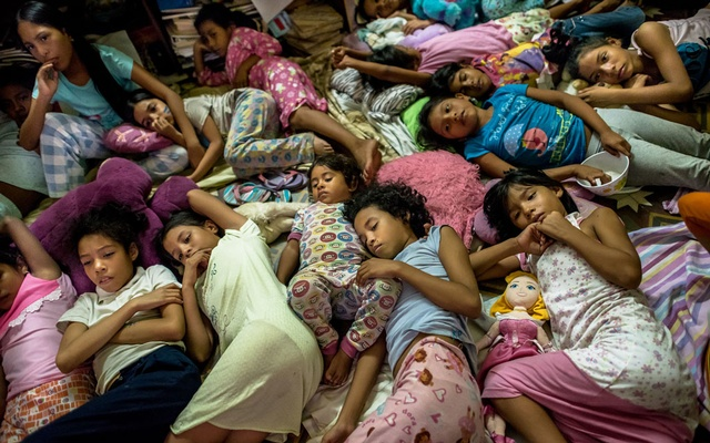 Ana, centre front, comforts one of the youngest girls while they watch a movie in their pajamas before bed, at the Casa Hogar Carmela Valera in Maracaibo, Venezuela on Feb 6, 2020. The New York Times