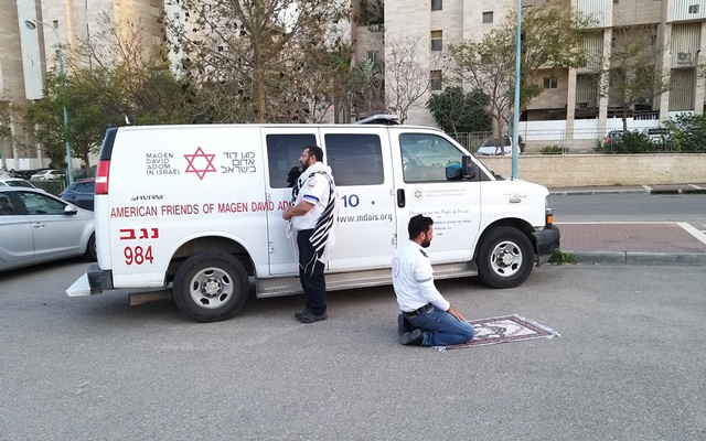 A pair of emergency medical technicians takes a moment to pray in Beersheba, Israel. The New York Times
