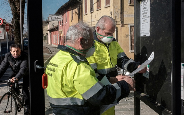 Life inside a red zone: Lombardy civil protection officers wearing protective masks put up posters in San Fiorano, one of the towns on lockdown due to a coronavirus outbreak, in this picture taken by schoolteacher Marzio Toniolo in San Fiorano, Italy, February 24, 2020. Picture taken February 24, 2020. Marzio Toniolo/via REUTERS