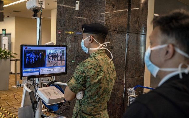 A soldier and medical worker screen body temperatures of arriving passengers at Changi Airport in Singapore, Feb 10, 2020. The New York Times