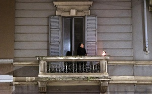 A women stands on a balcony in Milan on March 15, 2020. In Lombardy, Italian authorities are using cellphone location data to determine what percentage of people are obeying a lockdown order. The New York Times