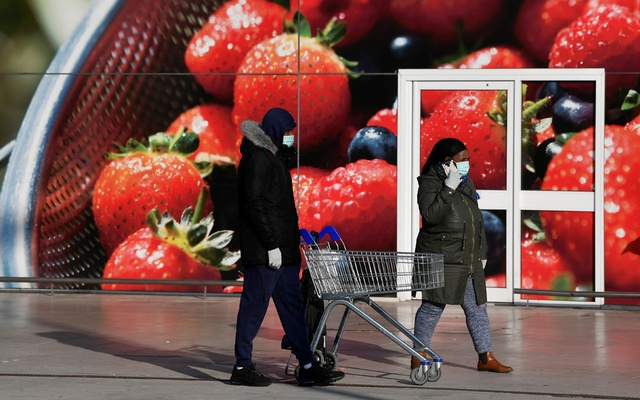 Shoppers wearing protective face masks queue outside a Tesco supermarket as they follow social distancing rules in West London as the spread of the coronavirus disease (COVID-19) continues, in London, Britain, Mar 26, 2020. REUTERS