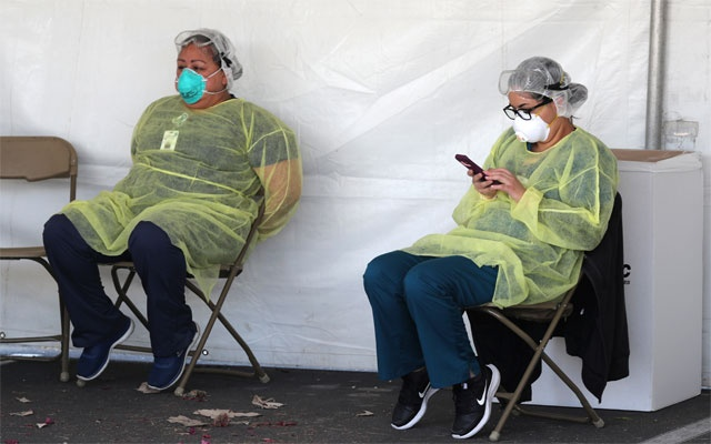 Hospital staff take a break between patients for drive-thru tests for coronavirus disease (COVID-19) in Indian Wells, California, US, March 26, 2020. Reuters