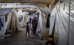 FILE -- Syrian families, displaced by recent fighting, living in tents underneath the stands of a sports stadium being used as an emergency shelter in Idlib, Syria, March 4, 2020. Crowded camps, depleted clinics and scarce soap and water make social distancing and even hand-washing impossible for millions of refugees. (Ivor Prickett/The New York Times)