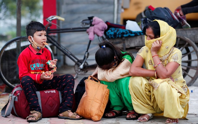 Aarti, wife of Sushil Kumar, a migrant worker, sits with her children along a highway as they wait for transport to return to their village, during a 21-day nationwide lockdown to limit the spreading of coronavirus disease (COVID-19), in Hapur, in the state of Uttar Pradesh, Mar 27, 2020. REUTERS